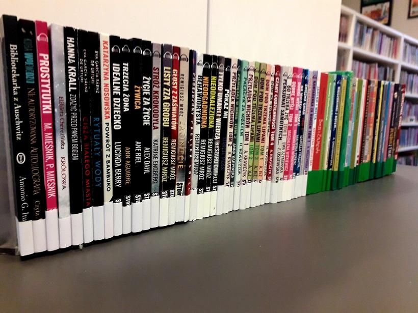 Obrazek przedstawia ustawione w rzędzie audiobooki, dla dorosłych i dla dzieci. Różne tytuły obrazują różnorodność audiobooków dostępnych w bibliotece.
