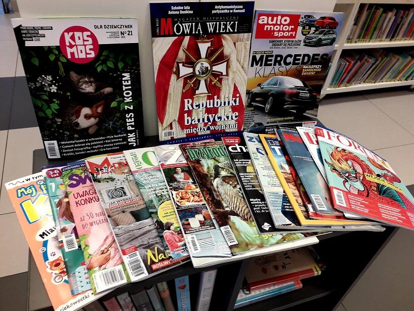 Obrazek przedstawia gazety ułożone na półce, są to czasopisma dla dorosłych i dla dzieci. Różne tytuły obrazują różnorodność czasopism dostępnych w bibliotece.